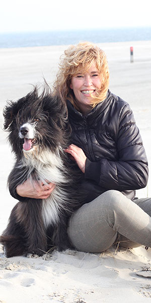 Astrid met haar hond Milo zittend op het strand
